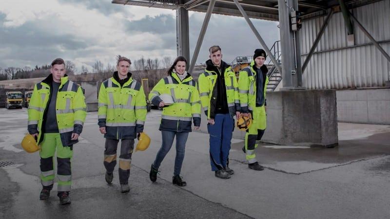 Fünf junge Menschen in signalgelber Arbeitskleidung auf Baustelle
