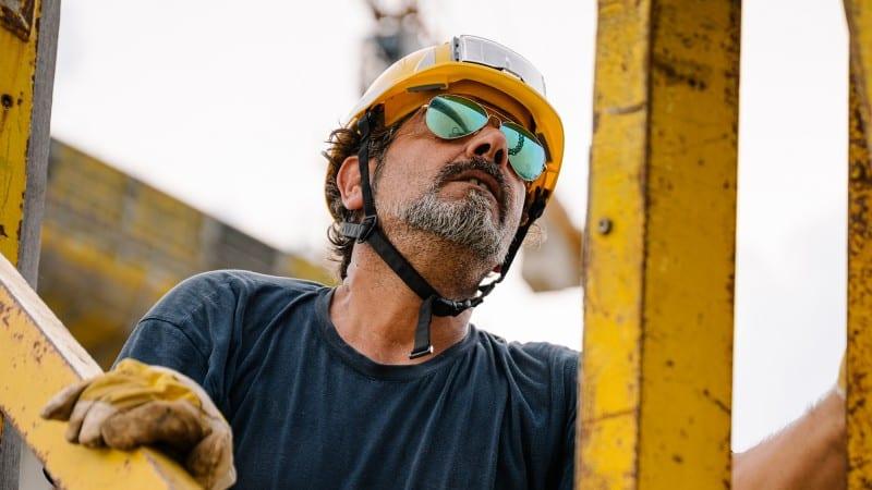 Etwa 50jähriger Mann mit Bauhelm, Bart und Sonnenbrillen bei der Arbeit