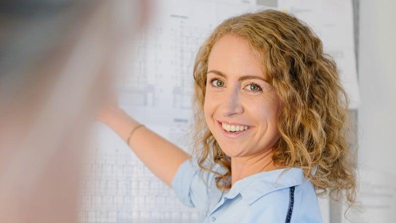 Blonde lächelnde Frau zeigt auf Bauskizzen an der Wand