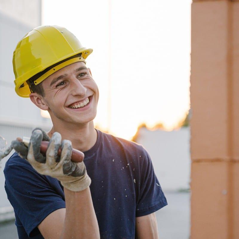 Junger lachender Mann mit Bauhelm bei Verputzarbeiten auf der Baustelle