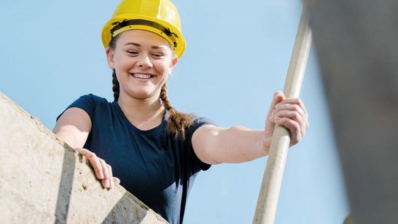 Junge, lachende Frau mit Bauhelm, die von einem Bauwerk herunterblickt