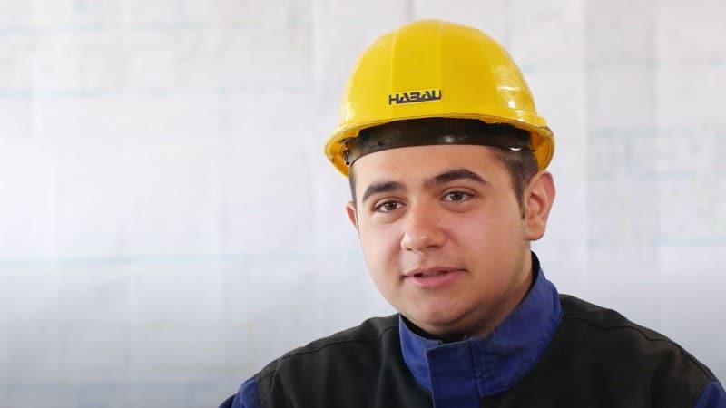 Porträt eines jungen Mannes in Bauhelm und Arbeitskleidung