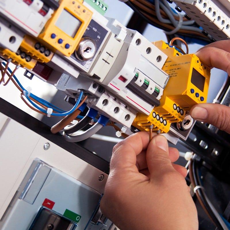 Detailaufnahme Hände an elektrotechnischer Anlage