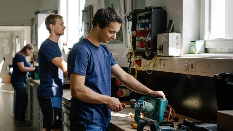 Drei Lehrlinge arbeiten in der Werkstatt