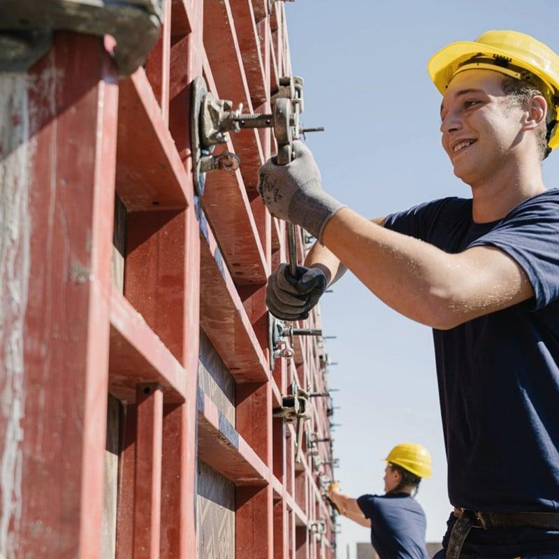 Junger Mann mit Bauhelm arbeitet an Betonrohbau