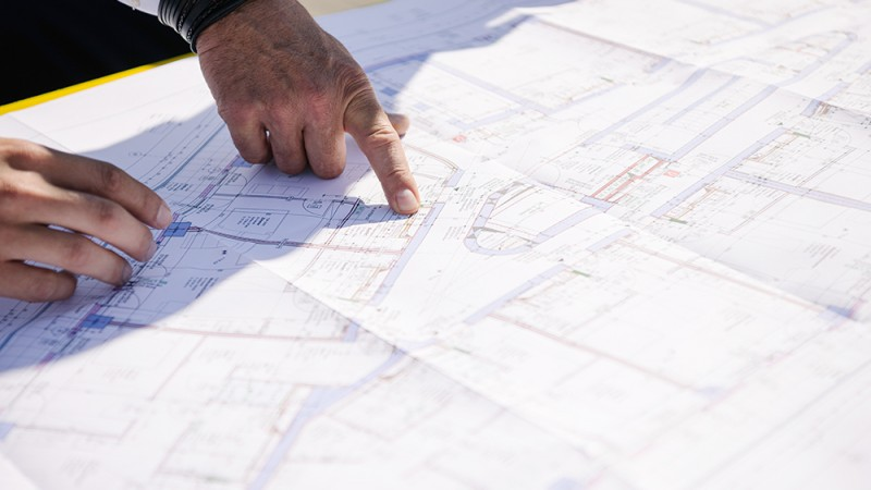 Hände zeigen auf Bauskizze