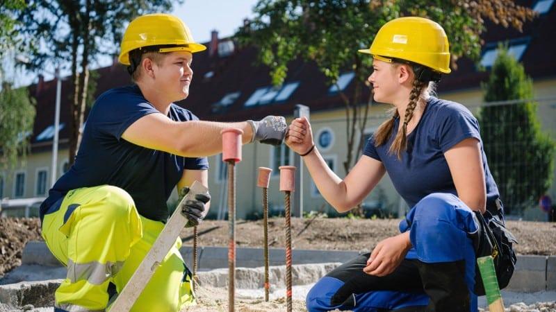 Lehre: Zwei jugendliche Lehrlinge mit Bauhelmen bei der Arbeit